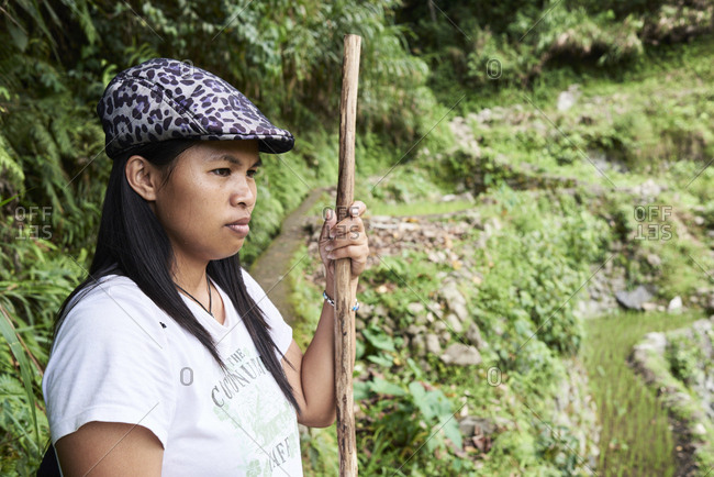 Batad, Philippines - March 3, 2018: female tour guide looking away focused in the jungle with walking stick and wearing hat.