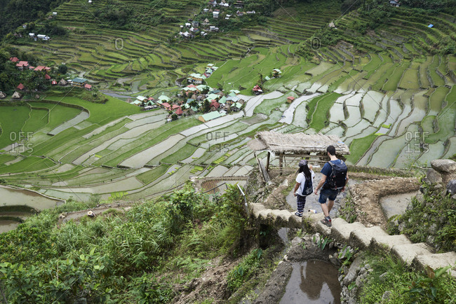Batad, Philippines - March 3, 2018: Tour guide and tourist walking downstairs with rice terrace views while in a private tour.