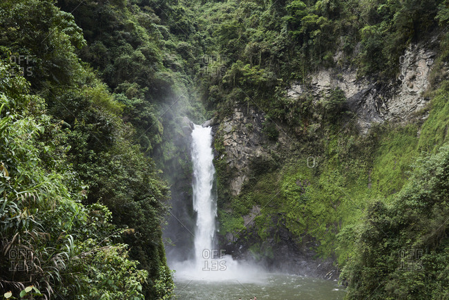 Beautiful raw waterfall surrounded by nature and vegetation located in Batad, Philippines.