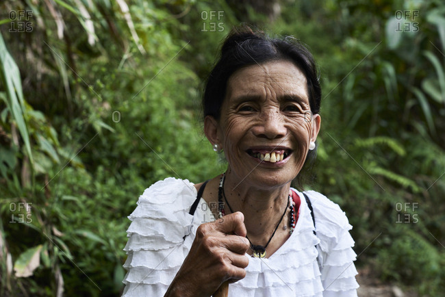 Batad, Philippines - March 4, 2018: Portrait of a happy senior filipina lady smiling at camera in the jungle with walking stick.