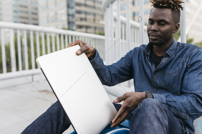 African man working with laptop at outdoors in Barcelona