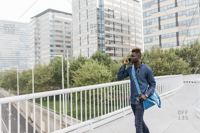 Young black man talking on mobile phone in Barcelona with city skyscrapers on background