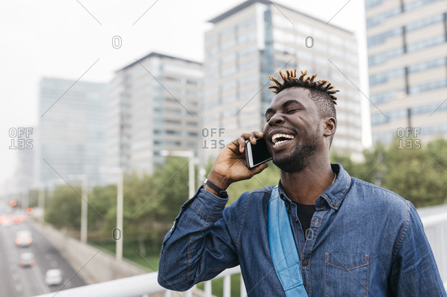 Young black man talking on mobile phone with a big smile in Barcelona with city skyscrapers on background