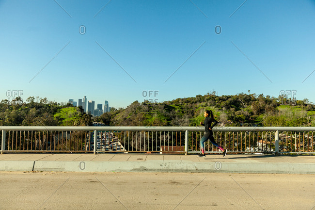 Woman running across bridge over busy freeway