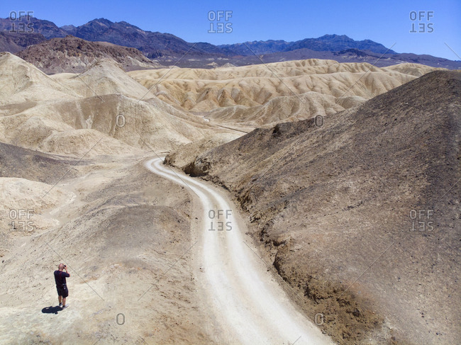 Tourist taking photograph along dirt road in the desert of Death Valley