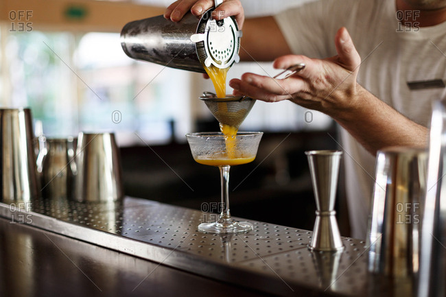 Bartender pouring orange juice through strainer