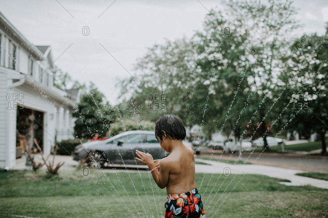 Boy playing in sprinklers in front yard