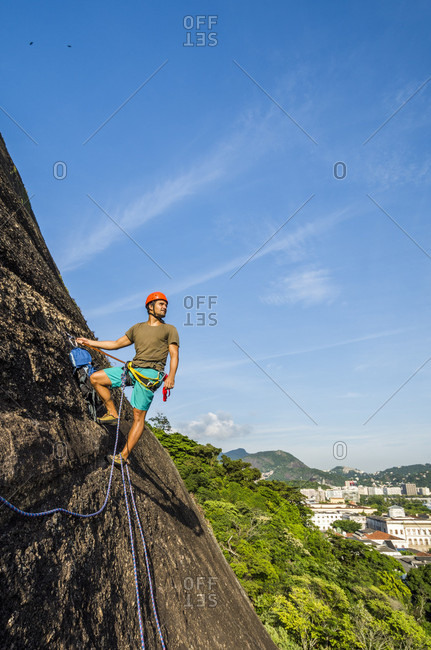 Young man ascending steep cliff with city buildings in background, Rio de Janeiro, Brazil
