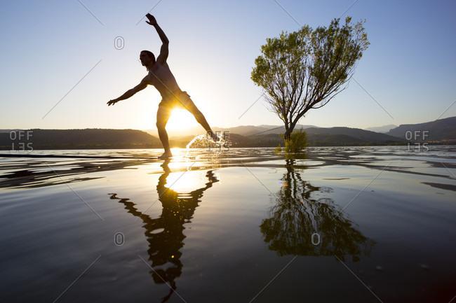 Silhouette of male slackliner crossing slackline tensioned over shiny lake at sunset, Pobla de Segur, Lleida, Spain