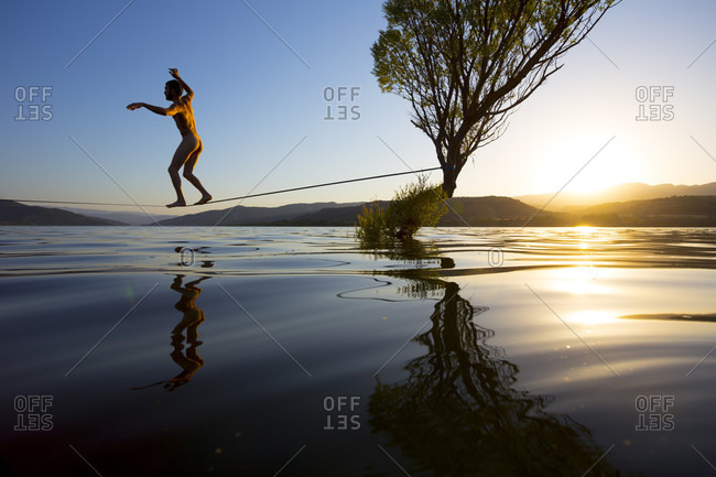 Nude man walking a water line at sunset in a very calm lake close to the Pyrenees
