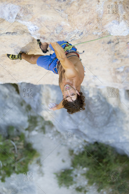 Male climber looking up while challenging Collegats Gorge shirtless, Pobla de Segur, Lleida, Spain