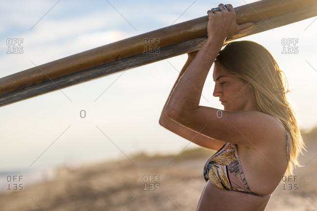 Side view of young woman in bikini with surfboard at beach