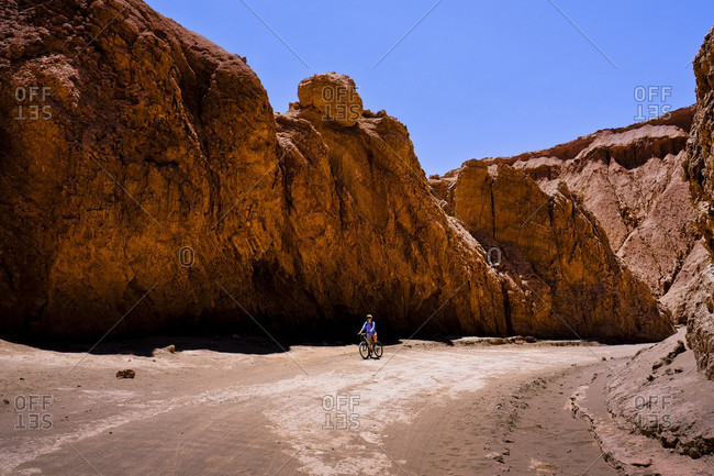 Adult woman riding bicycle in Death Valley during sunny weather, Chile