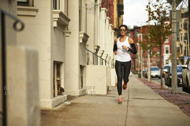 Young woman jogging on pavement along city street, Boston, Massachusetts, USA