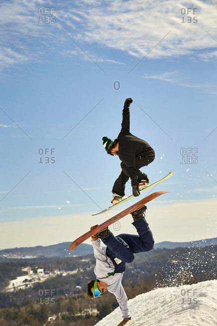 One snowboarder airs over another doing a handplant in the terrain park