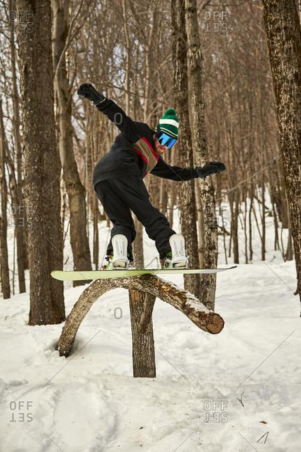 Snowboarder sliding on wooden feature in terrain park, Vermont, USA