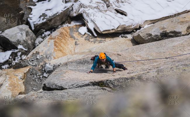 View from above of adventurous rock climber climbing Bienvenue au Georges V route, Pointe des Nantillons, Alps, Haute-Savoie, France
