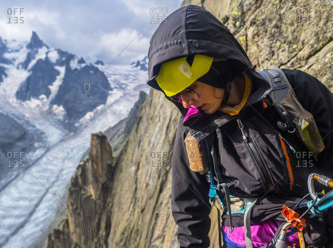 Waist up shot of female rock climber in hooded jacket looking down in French Alps, Aiguille du Grepon, Haute-Savoie, France