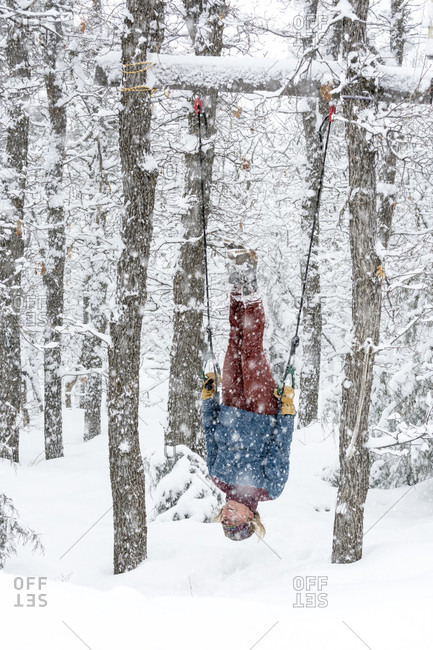 Adult woman hanging upside down on outdoor gymnastic rings during snowstorm, Durango, Colorado, USA