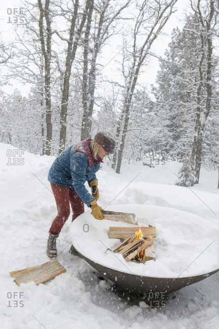 Adult woman burning firewood in outdoor fire pit during snowstorm, Durango, Colorado, USA