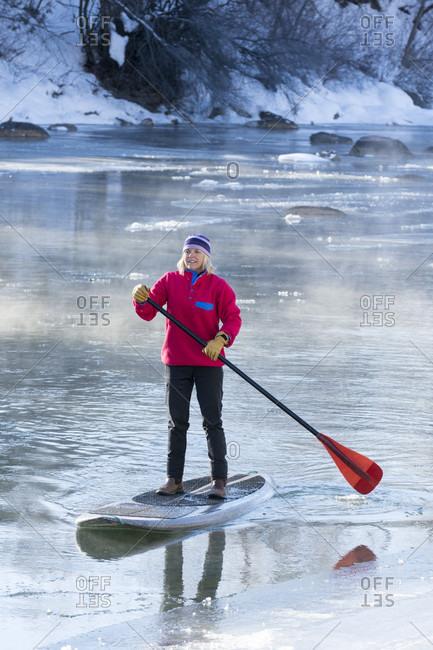 Adult woman paddleboarding across icy Animas River during winter, Durango, Colorado, USA