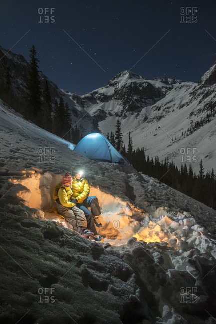 Mother and daughter embracing on snow in front of campfire while camping in snowcapped mountains ta night, Silverton, Colorado, USA