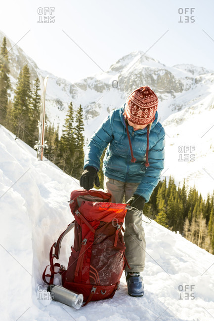 Young girl packing backpack while winter camping in snowcapped Arastra Gulch mountain pass, Silverton, Colorado, USA