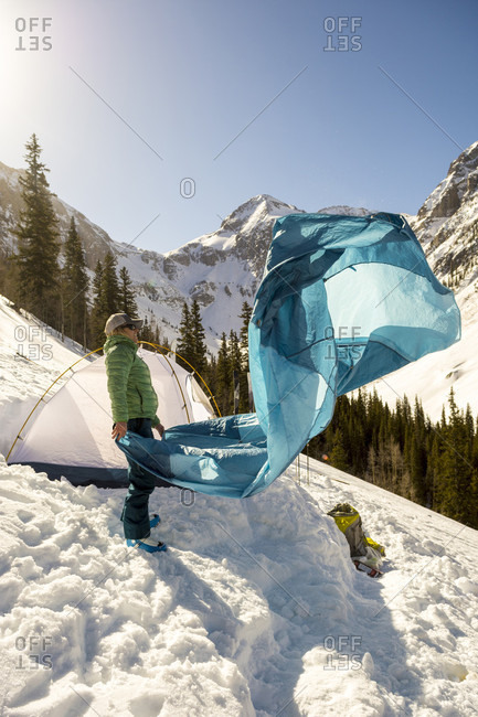 Adult woman packing up tent after winter camping in snowcapped Arastra Gulch mountain pass, Silverton, Colorado, USA