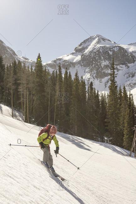 Young girl skiing alone in snowcapped Arastra Gulch mountain pass, Silverton, Colorado, USA