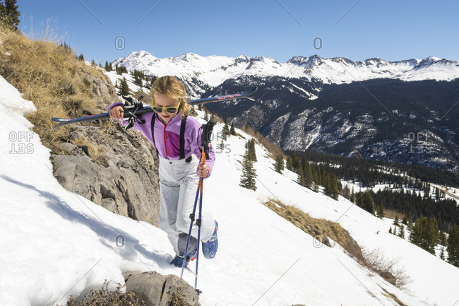 Young girl carrying skis up snowy hill before skiing in Molas Pass, Silverton, Colorado, USA
