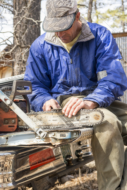 Man sharpening chainsaw on tailgate of old farm truck, Durango, Colorado, USA