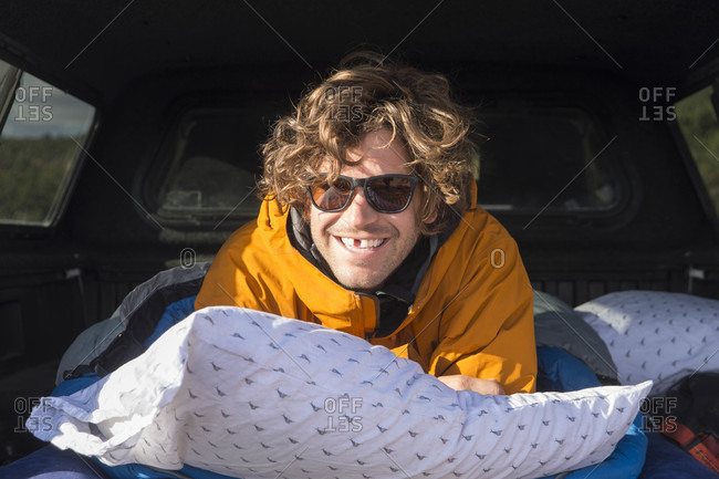 Portrait of man wearing sunglasses smiling at camera while lying on pillows inside car, Moab, Utah, USA