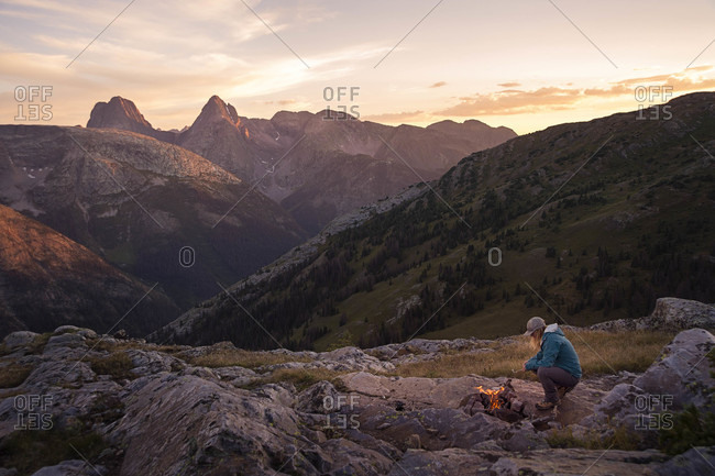 Woman with campfire in San Juan mountains at sunset, Silverton, Colorado, USA