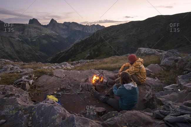 Couple sitting around campfire in San Juan mountains at sunset, Silverton, Colorado, USA