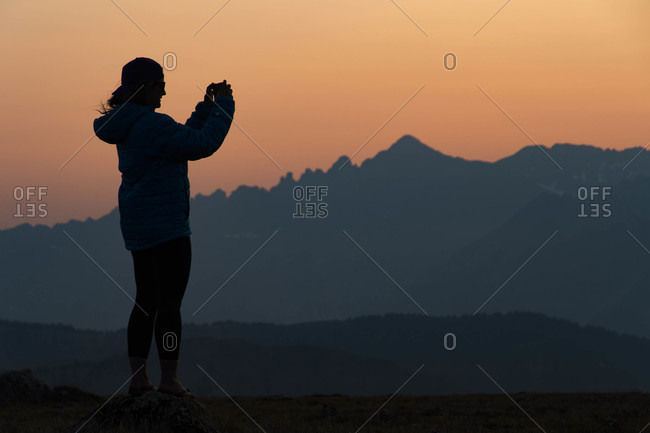 Woman taking picture with smartphone in mountains at sunset, Aspen, Colorado, USA