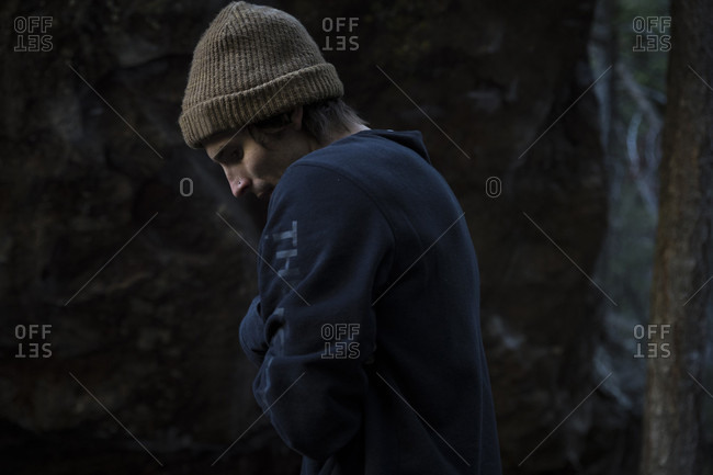Side view of young man in knit hat and sweatshirt standing outdoors in cold