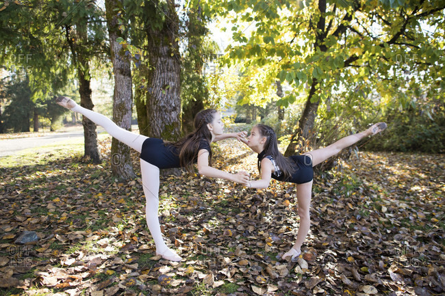Side view of two girls in leotards dancing ballet in forest