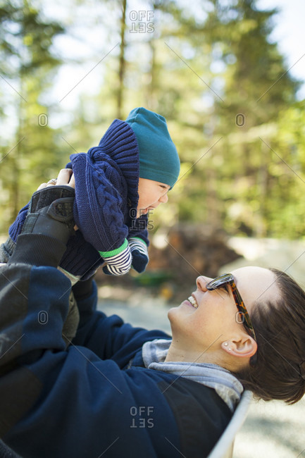Side view of mother holding baby in knit hat and sweater aloft