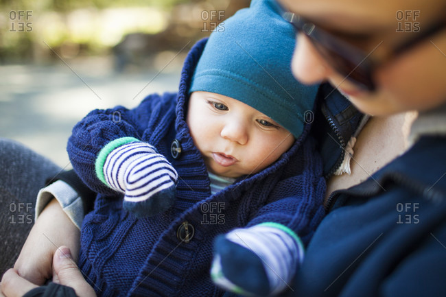 Mother holding baby boy in knit hat and sweater