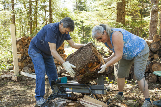 Couple splitting firewood using wood splitter machine