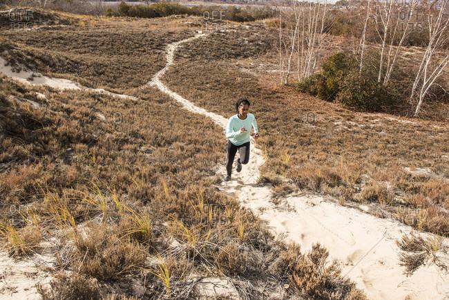 Young woman jogging on narrow sandy path on sunny day, Newburyport, Massachusetts, USA