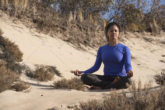 Young woman meditating barefoot on sandy terrain during sunny weather, Newburyport, Massachusetts, USA
