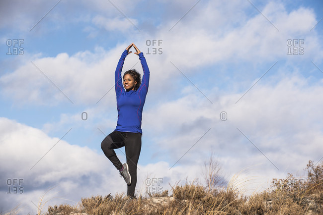Young female yoga practitioner standing against clouds on one leg with raised arms, Newburyport, Massachusetts, USA