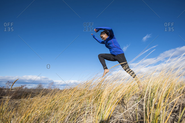 Young woman running and jumping on grass barefoot, Newburyport, Massachusetts, USA