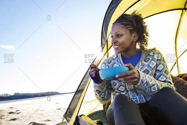 Young woman sitting in tent and eating breakfast while camping on coastal beach, Newburyport, Massachusetts, USA