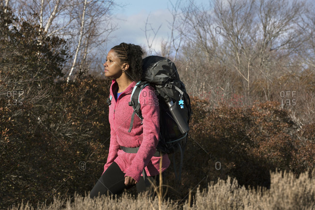 Young woman hiking with backpack in front of various bushes, Newburyport, Massachusetts, USA