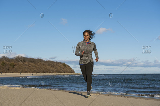 Young woman jogging on sandy beach along ocean coastline, Newburyport, Massachusetts, USA