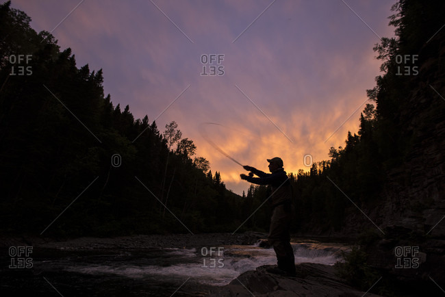 Fly fisherman casting into Le Chutes pool on York River at sunset, Gaspe, Quebec, Canada