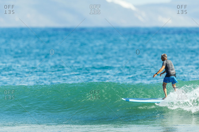 A man surfing a longboard on a wave on a sunny day at TeaTree Point in Noosa National Park