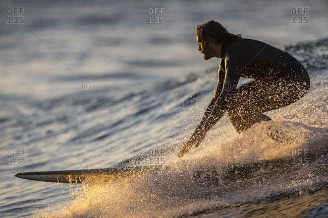 A surfer riding a wave on a longboard around sunset at Noosa National Park